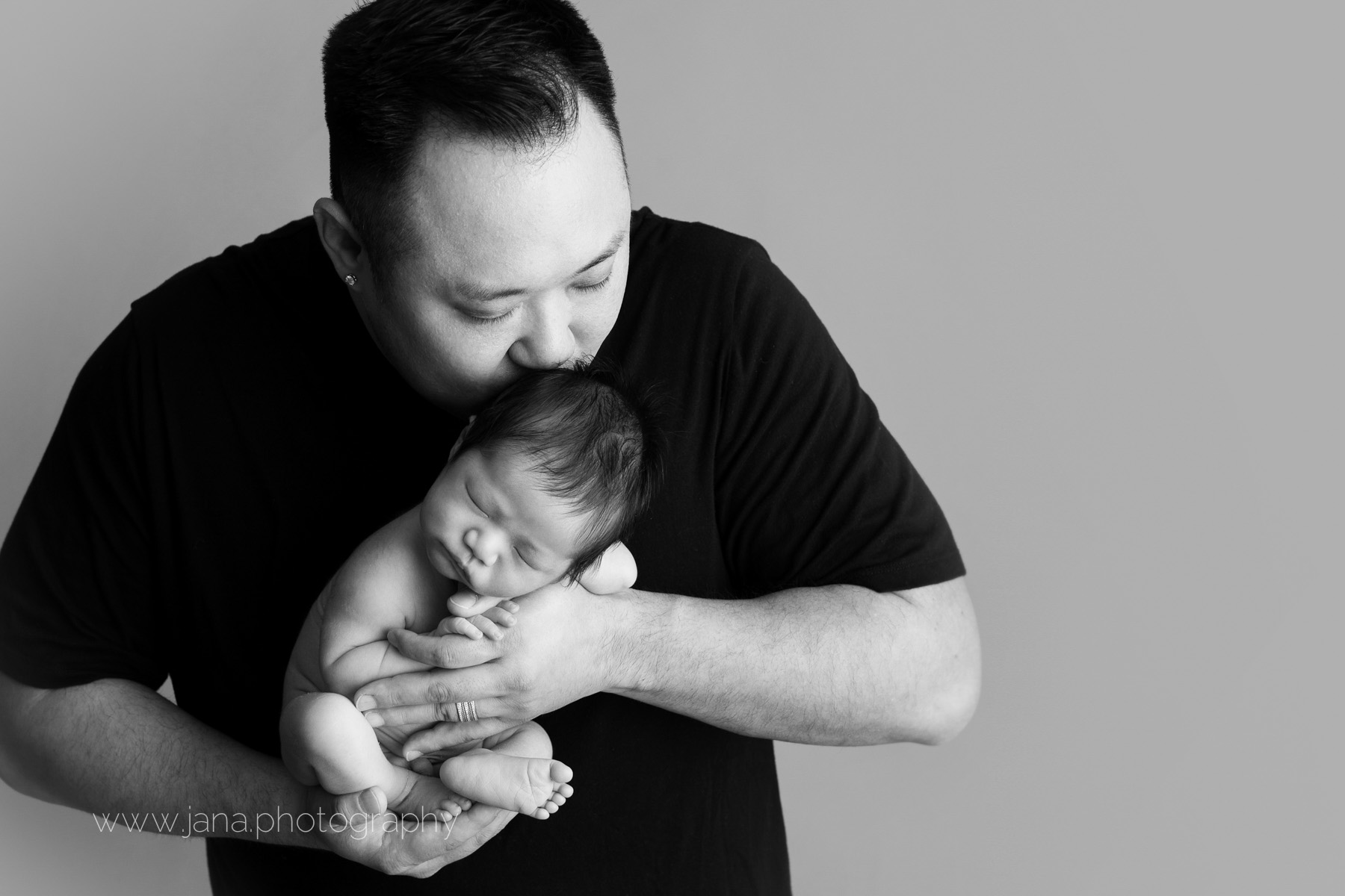 Newborn photography - dad kissing - black and white