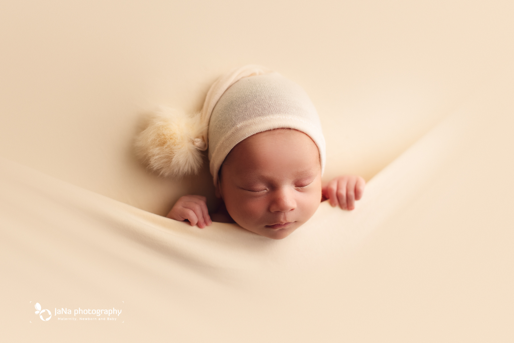 newborn baby boy sleeping on a cream background wearing hat