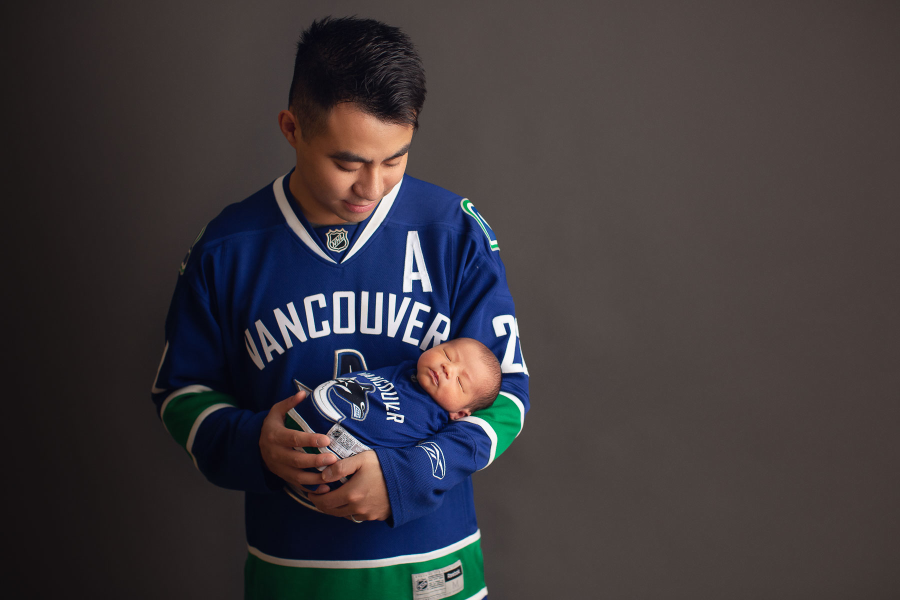 Vancouver Canucks newborn photography - daddy and son Canucks outfit