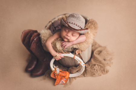 newborn baby boy with a cowboy outfit