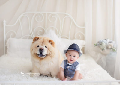 cute baby boy taking picture with his dog