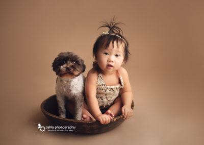 cute baby girl taking picture with her dog