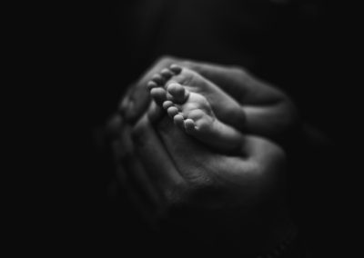 black and white newborn baby feet and dad hand | jana newborn photography