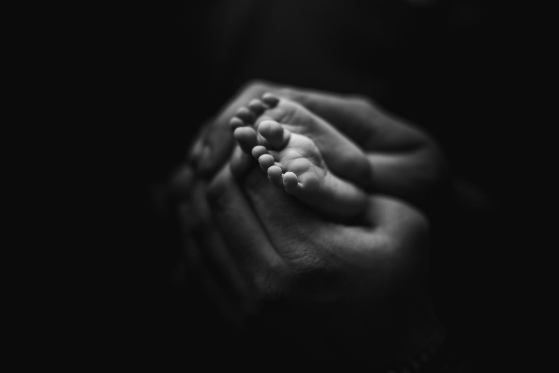 black and white newborn baby feet and dad hand | jana newborn photography