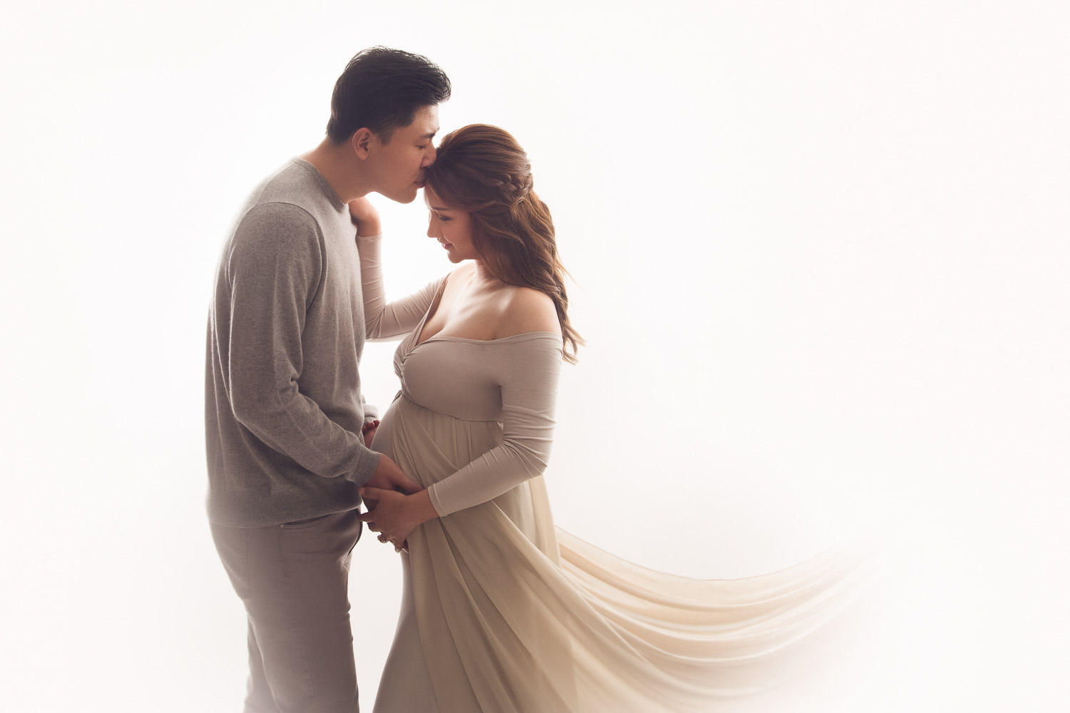 loving husband kissing his wife forehead during their maternity photography session