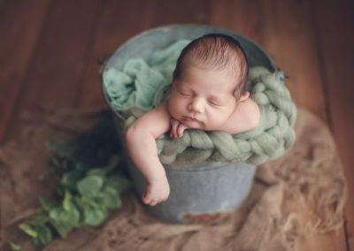 baby boy in green bucket | jana newborn photography
