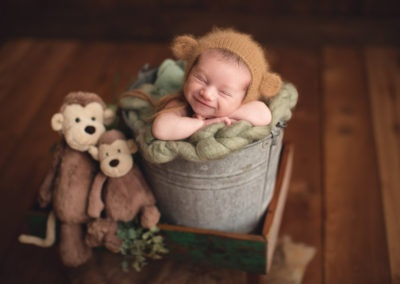 Vancouver newborn photography baby boy in a brown bucket and smile