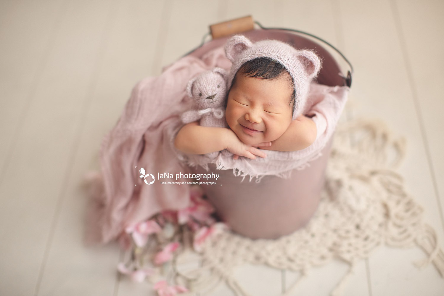 newborn baby girl in a pink bucket smiling | jana photography