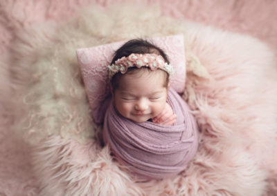baby girl smile in a pink fur | jana newborn photography
