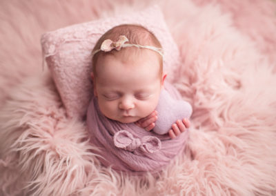baby girl in a pink fur holding heart | jana newborn photography