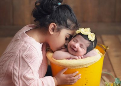 newborn-baby-girl-sister-sibling-yellow