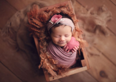newborn photography vancouver - baby girl smile and hold pink heart