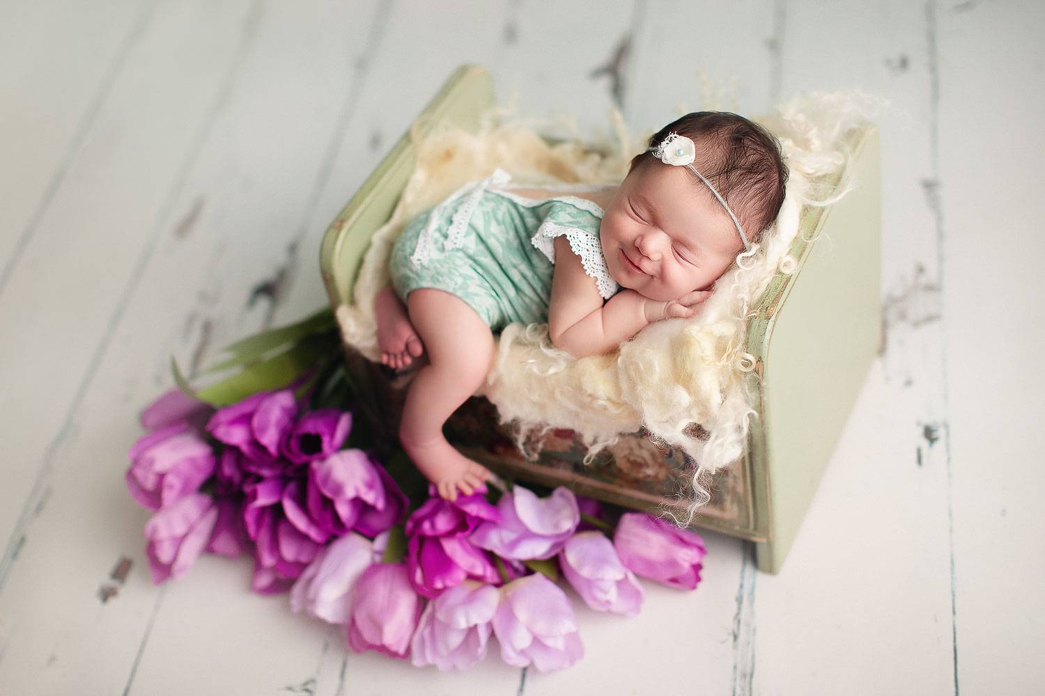 newborn photography | baby girl with a green outfit smiles | tulip