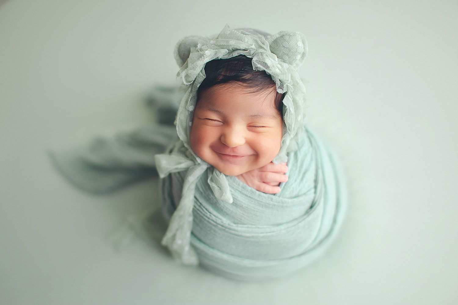 newborn photography | baby girl smile in a green background