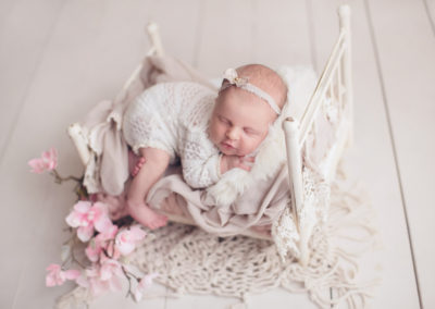 newborn-baby-girl-white-bed-smile-jana-photography