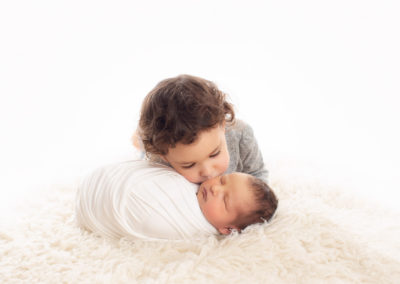 sibling and newborn baby boy kissing | Jana photography