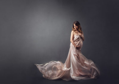 pink silk maternity picture and artistic fabric toss in studio