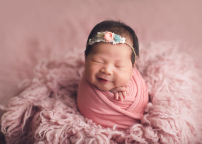 newborn photography vancouver | baby girl smile in a pink fur