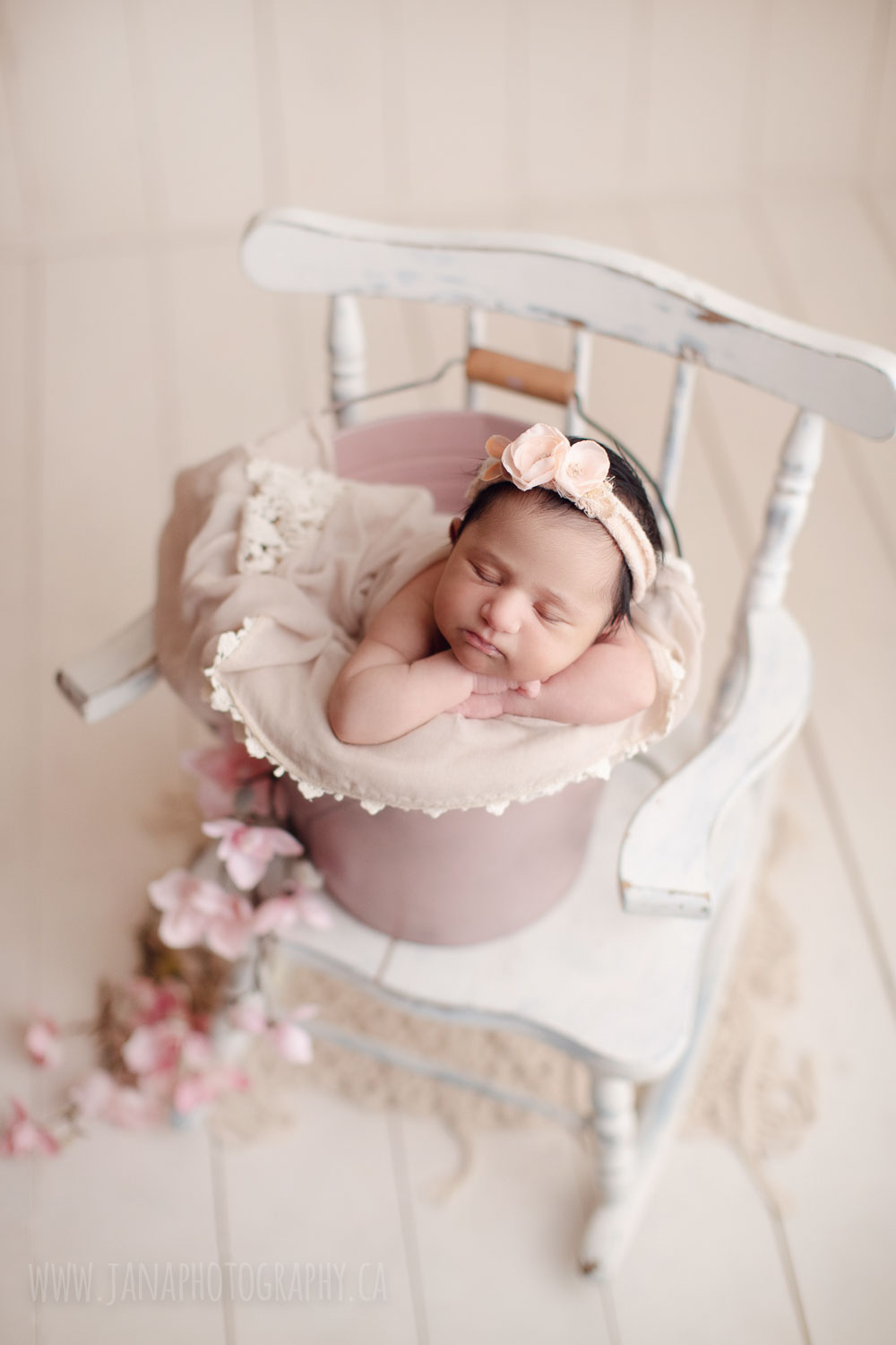 newborn baby girl in a pink bucket and white chair - Vancouver - janaphotography