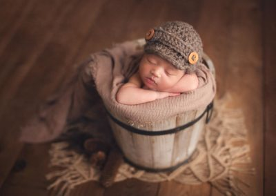 newborn baby boy in a brown setup with hat