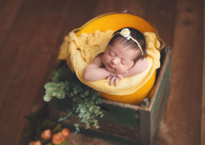 newborn photography baby girl in a yellow bucket smiling