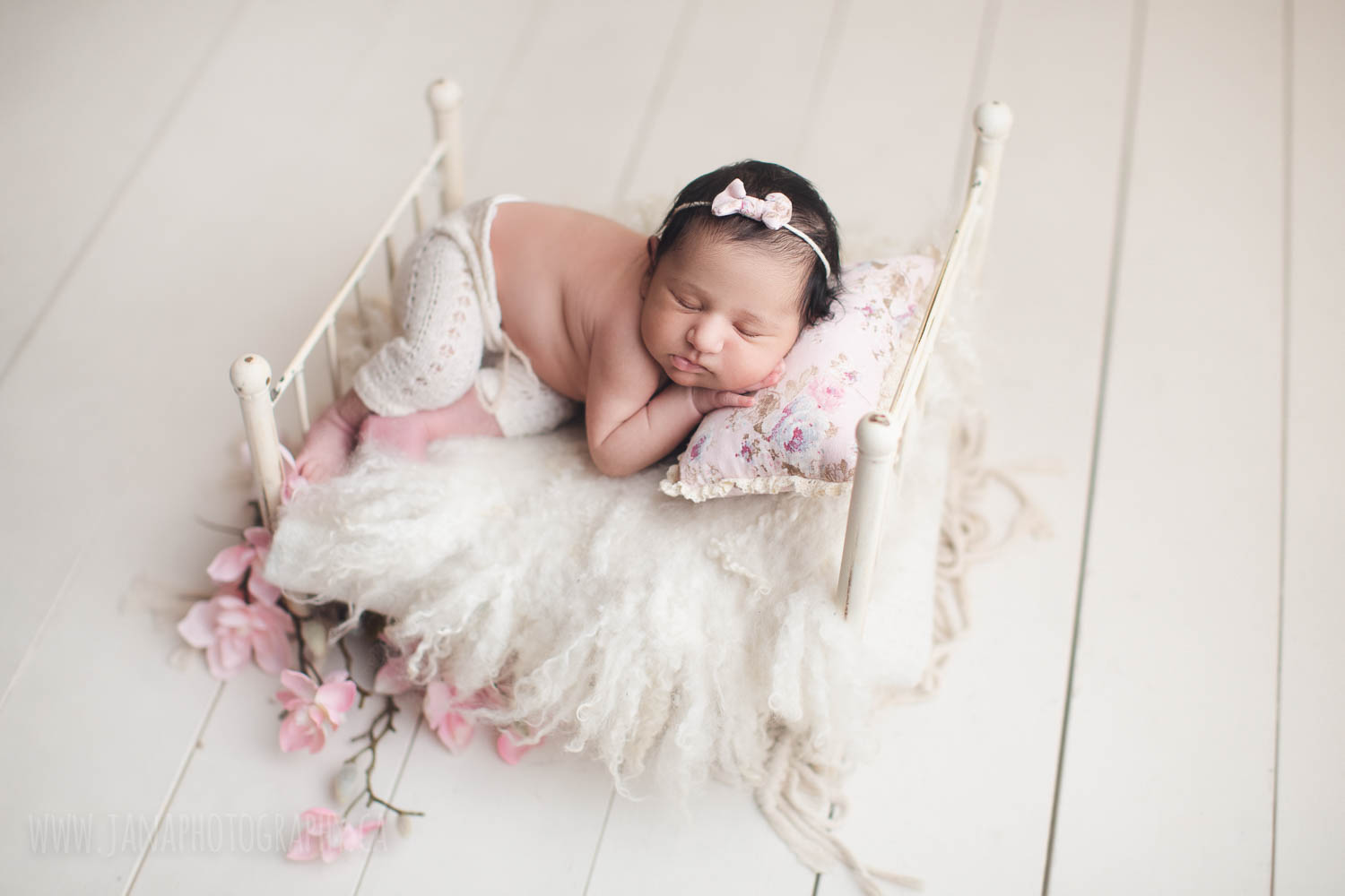 newborn photography - baby girl sleeping in a white bed