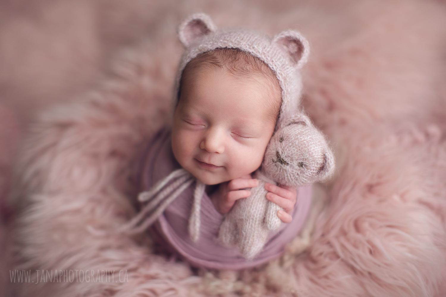 baby girl smiling in a pink background - holding a bear