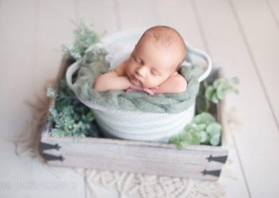 newborn baby boy in white an green bucket