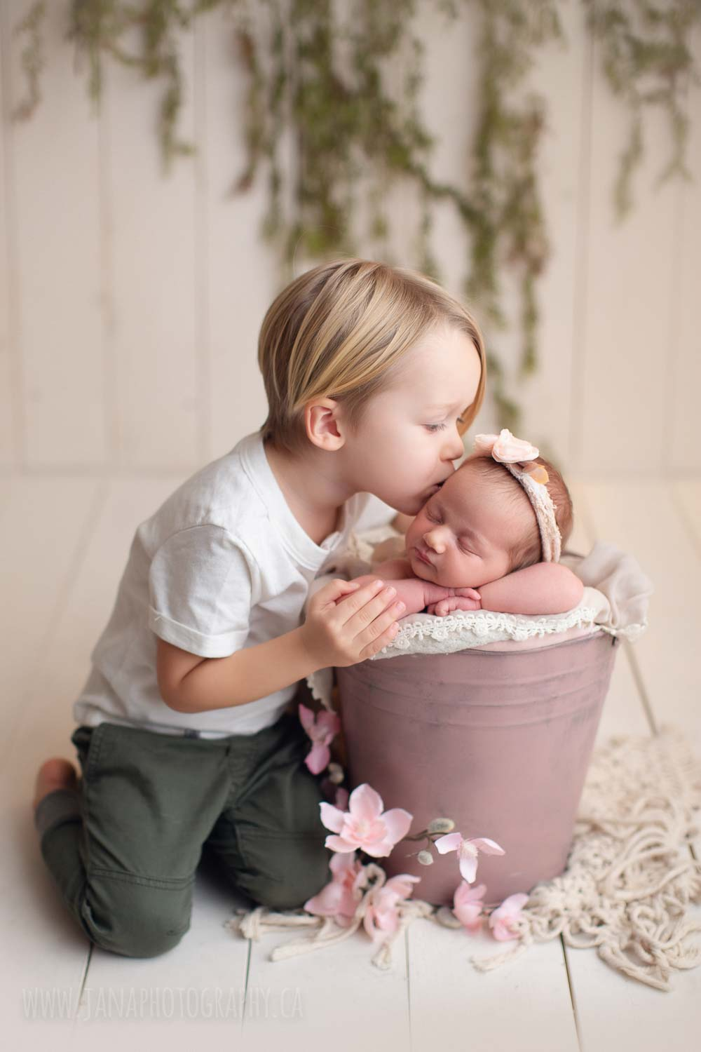 baby brother is kissing newborn girl sister in a pink bucket