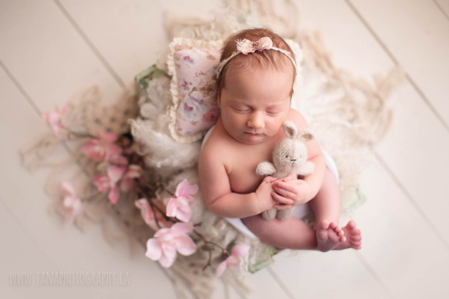 baby girl is holding teddy bear - bunny in a white bed - newborn photography burnaby