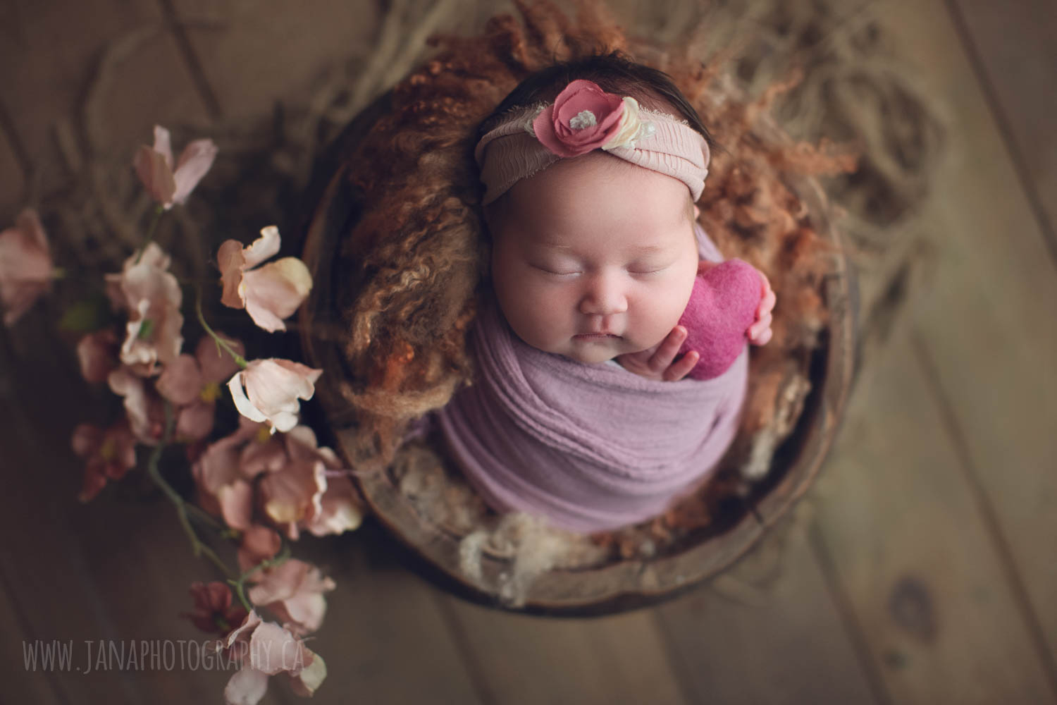 newborn baby girl is holding pink heart - newborn photography vancouver jana