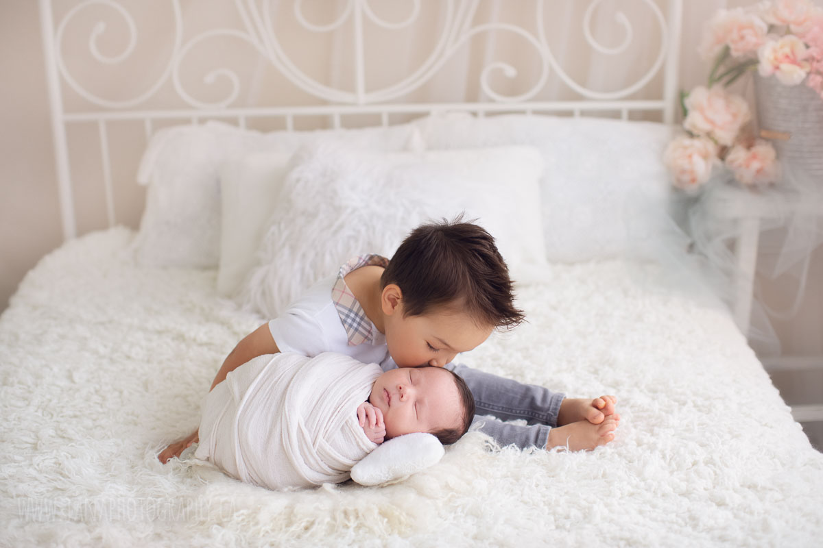 baby brother is kissing his newborn baby - natural light bed