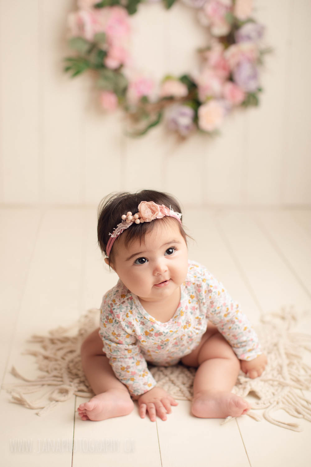 Baby girl sitting with headband and floral pink dress