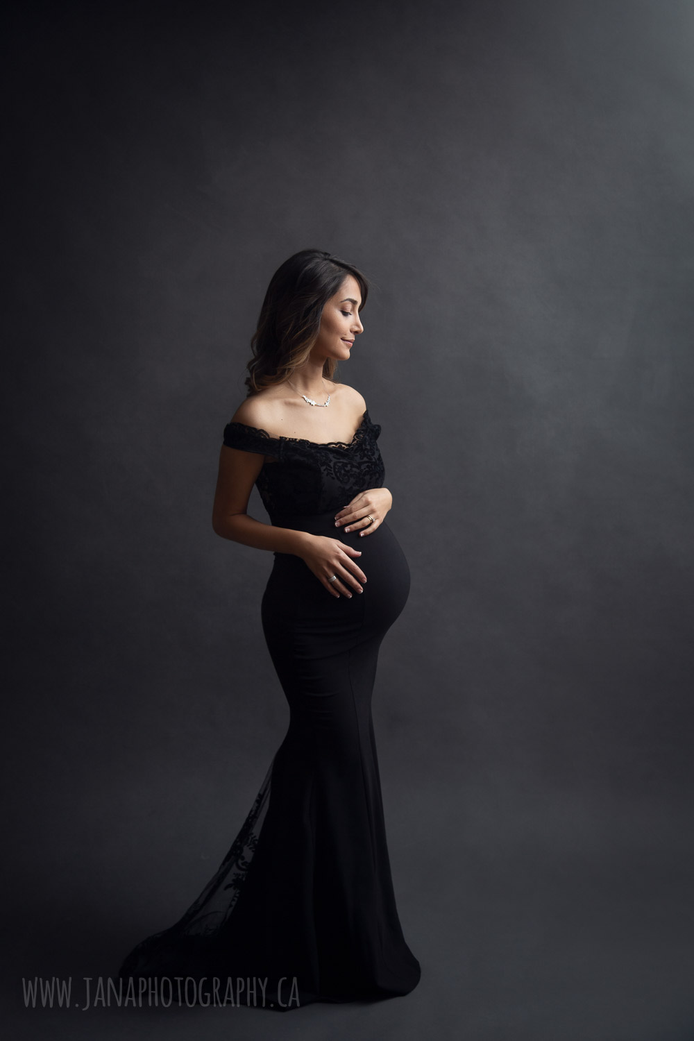 Pregnant woman with black dress in maternity photo black background
