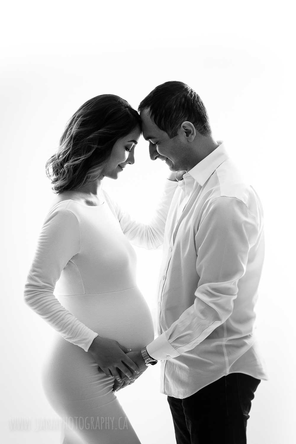 Mom and dad maternity photo in front of each other in black and white