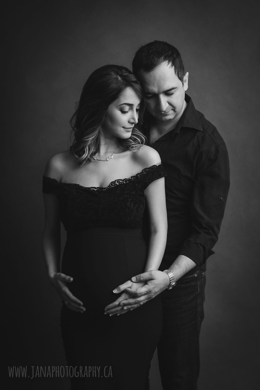 Black and white maternity photography mom standing in front of dad looking down