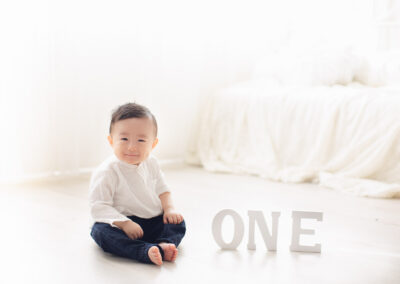 one year old boy in white background sitting on the floor dreamy background
