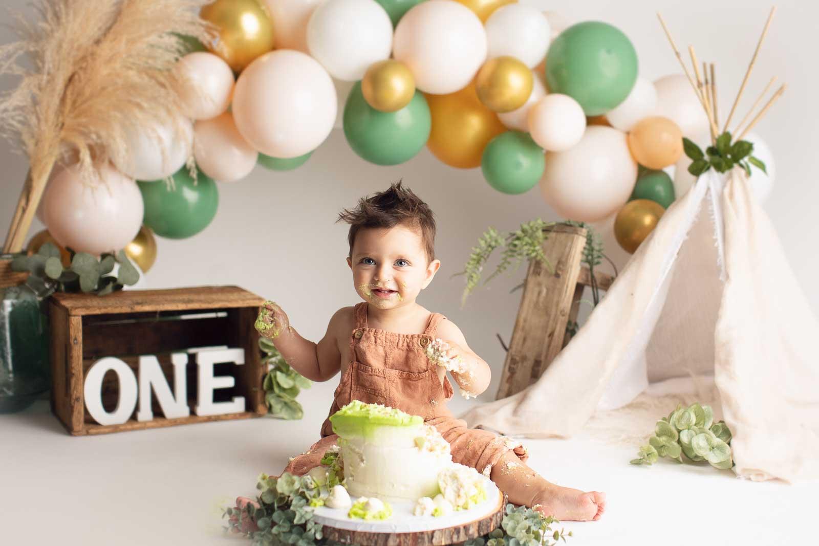 blond boy smashing cake in pastel green colour background
