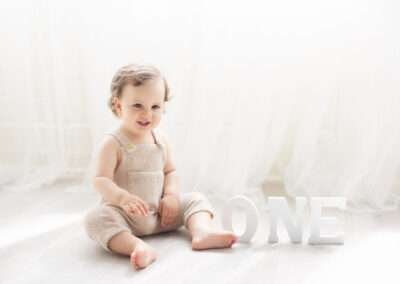 one year old boy in a timeless white background