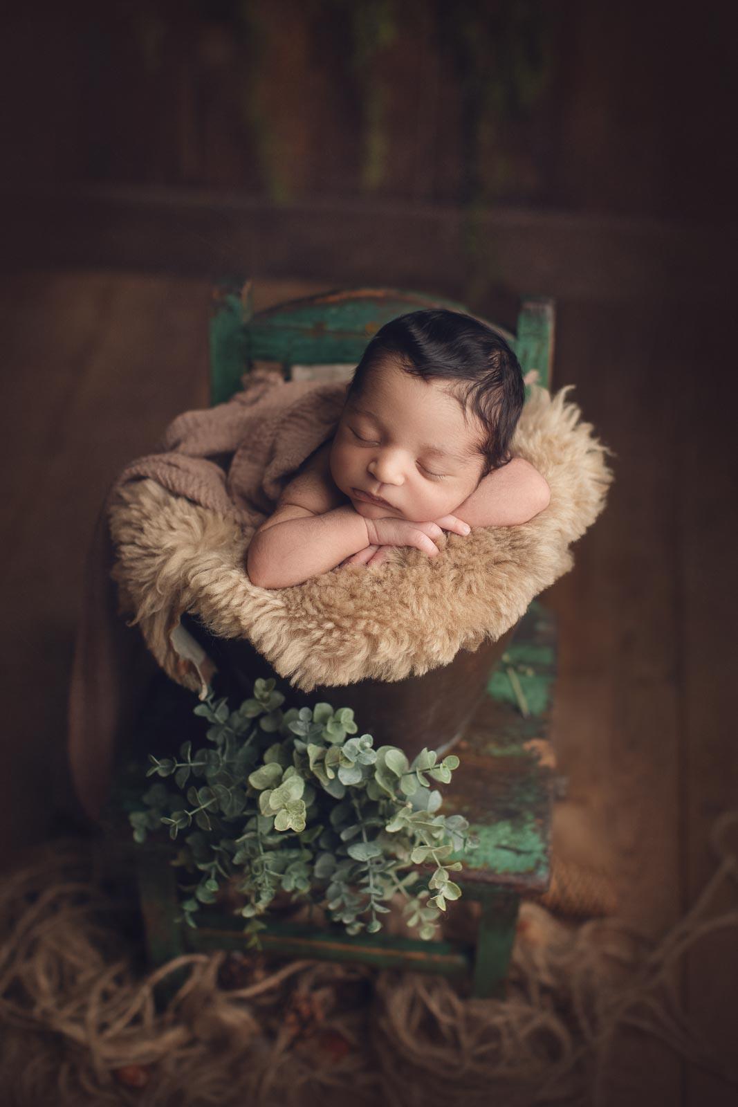 newborn in brown bucket