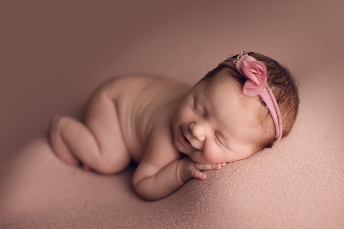 how to make baby smile - newborn pink background