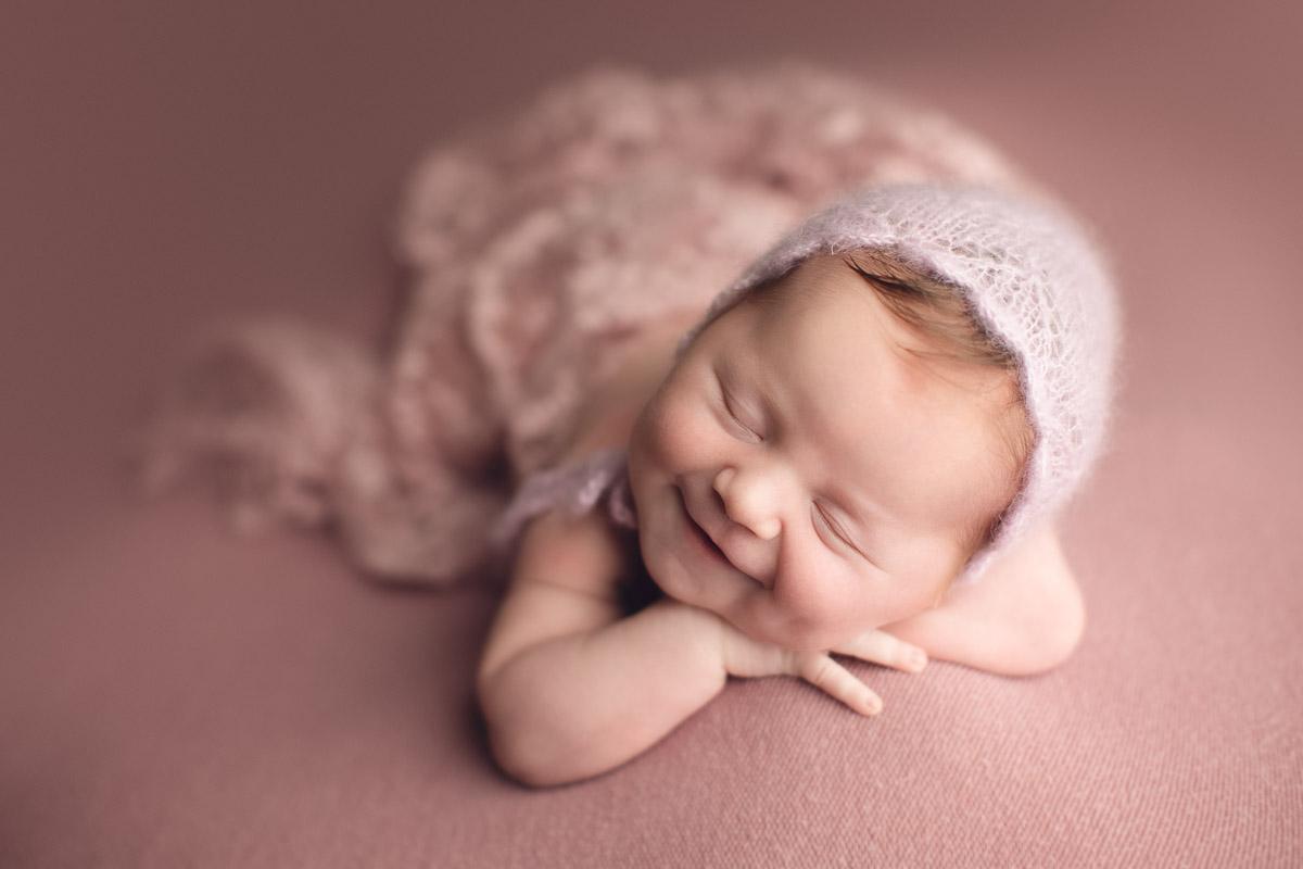 newborn baby girl smiles - hat - pink background