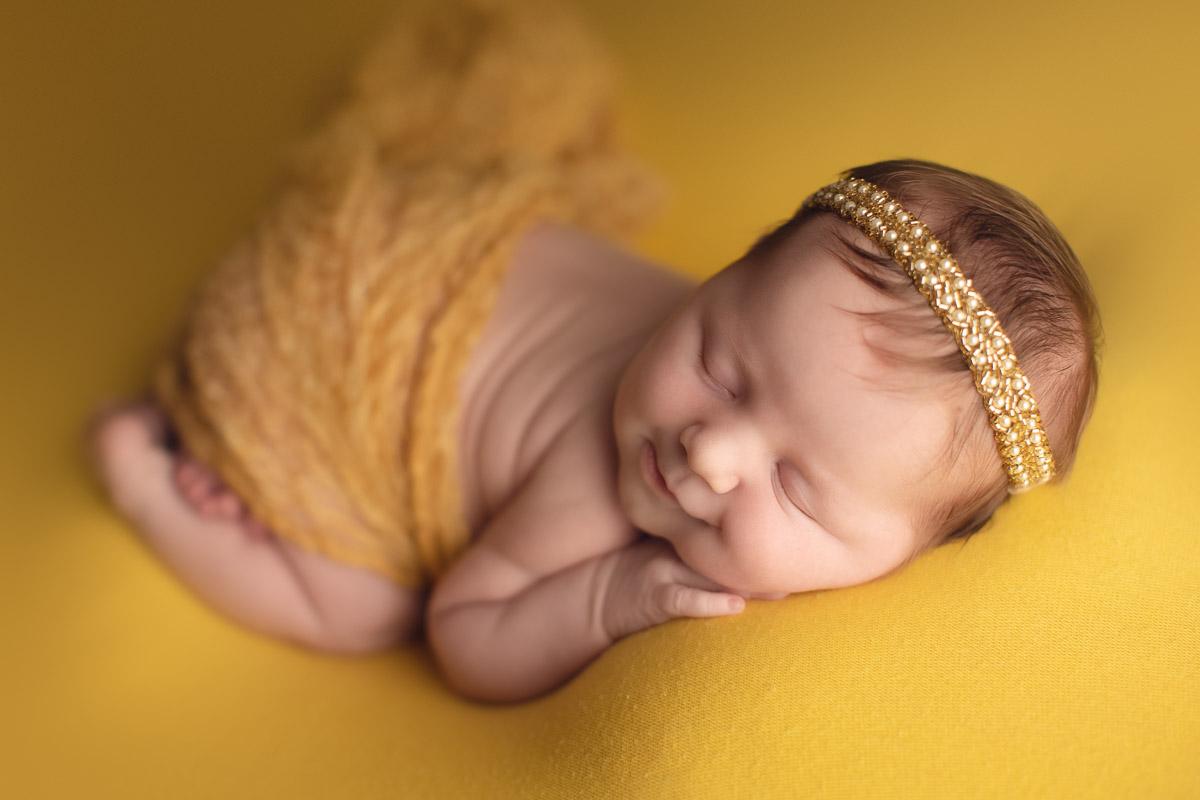 newborn baby girl - smile - yellow background